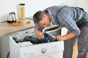 Handyman Checking Washing Machine With Flashlight